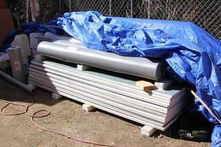Dwell Home Venice: Part 14 - Photo 3 of 9 - Stacked roofing materials ready to be installed, including rolls of Versiflex PVC material and sheets of Securock roofboard for use with rooftop gardens. All roofing materials will be installed by JT Harris Inc.