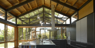 The house has a variety of indoor and outdoor spaces where the family can hang out, including a soaring kitchen and, through a big glass-walled door, an outdoor dining pavilion shaded by a vine-covered arbor.