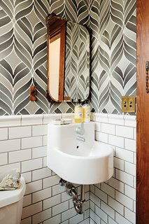 Playful wallpaper from Graham & Brown livens up the house's otherwise staid <br><br>powder room, which also contains a <br><br>pint-size Ikea sink.