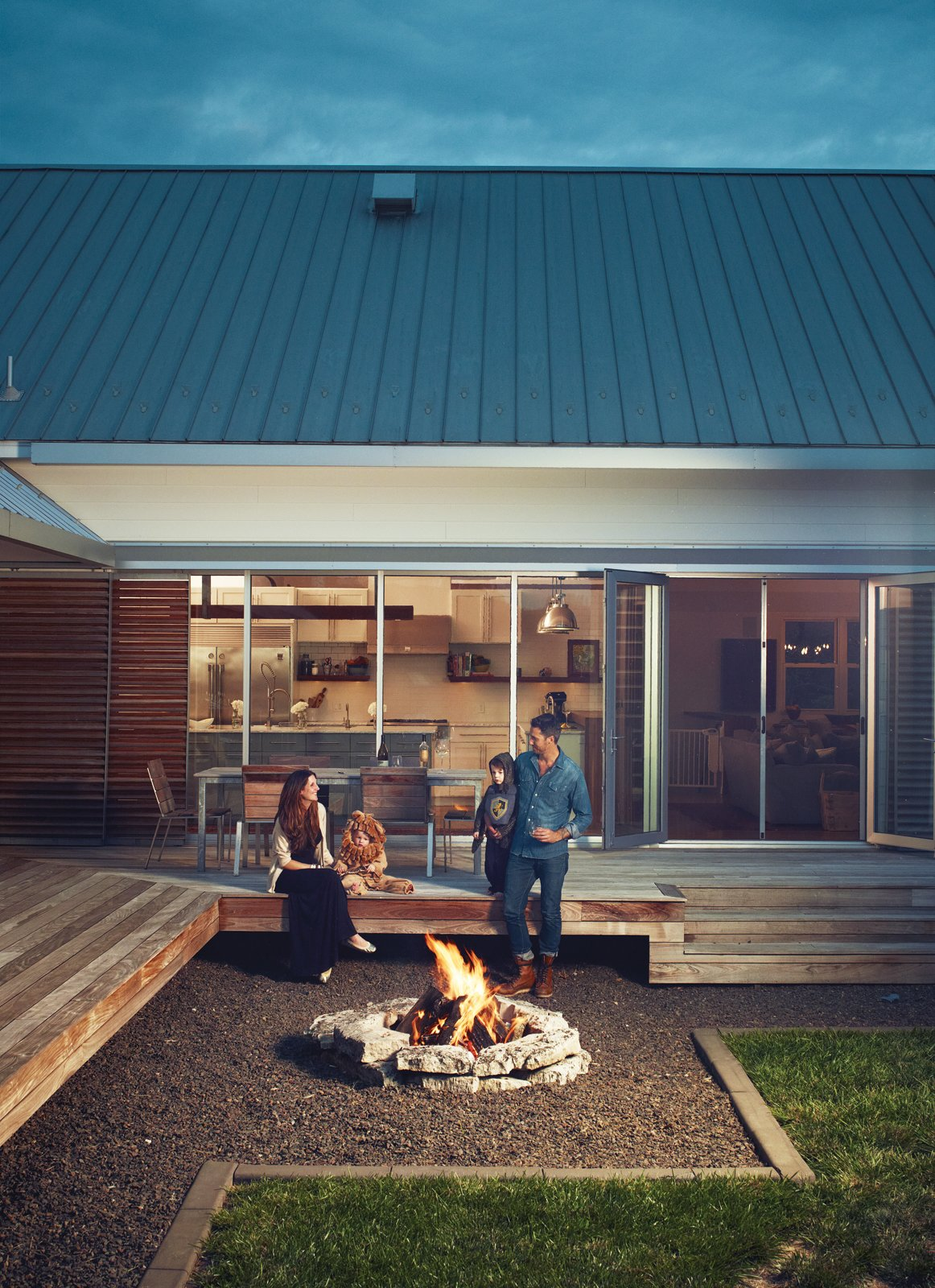 """Outdoor, Back Yard, Large Patio, Porch, Deck, and Grass Though the fire pit was """"kind of an after-thought,"""" says Hannah, the family uses it year-round. """"In the spring and fall, it warms you up on cool nights, and in the summer, it just adds ambience.""""  Photo 3 of 10 in A Modern Farmhouse Recalls Old-Time Americana"""