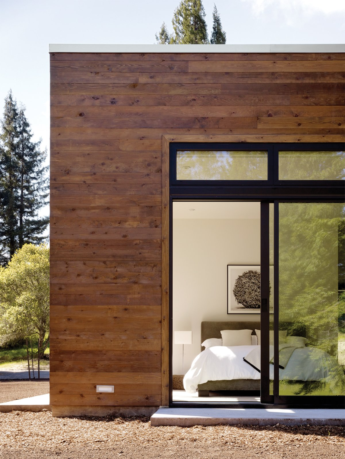 Bedroom and Bed The modestly scaled master bedroom opens to a view of the woods located behind the property.  Photo 4 of 5 in This Couple Achieves Their Glass House Goals