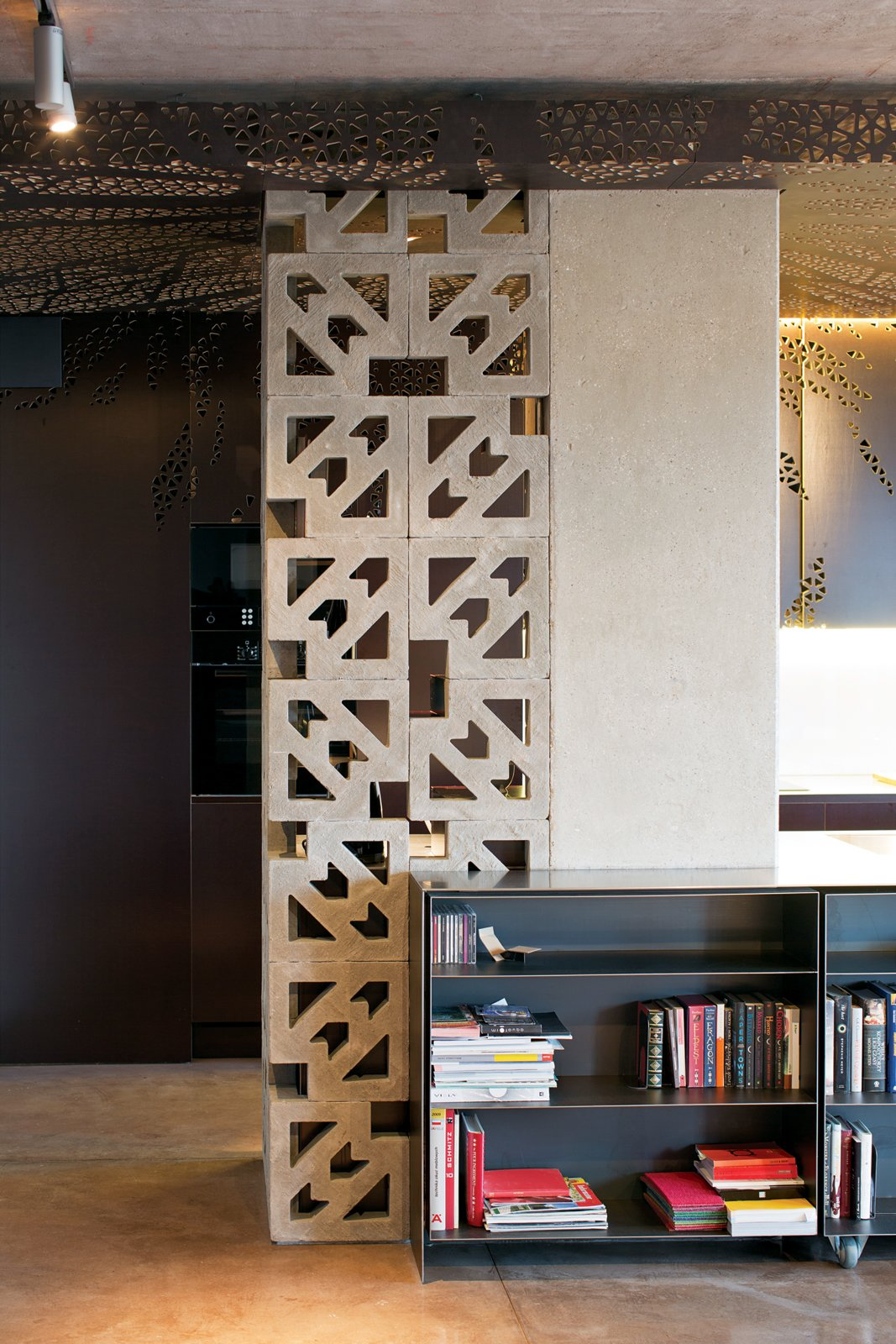 """Storage Room and Shelves Storage Type Ornate concrete blocks screen a storage area in the kitchen while letting light through. The effect is """"romantic—romantyczny,"""" says Nix.  Photo 5 of 9 in Warsaw Loft with Multifunctional Furniture"""