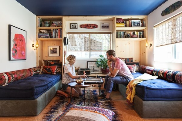 Howard and Shumate in the living room, where Commune designer Steven Johanknecht introduced custom built-in daybeds with storage beneath. The carpet-fragment pillows are from Commune, as is the table, designed by Joshua Tree–based sculptor Alma Allen. The poster is by Mike Mills.  Photo 2 of 7 in A Modern Beachside Trailer Home in Malibu