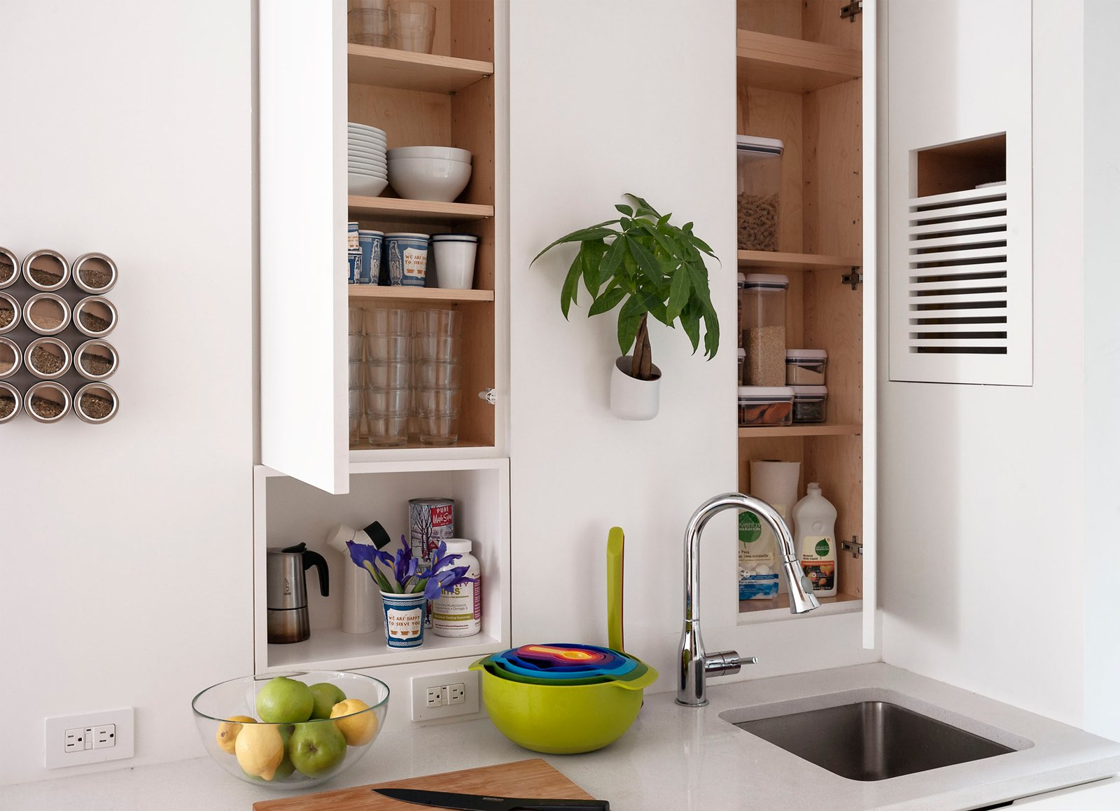 In the kitchen, a metal wall allows for a variety of magnetic accessories, such as a spice collection and stylish planter. LifeEdited favors stacking dishes and nesting bowls to help conserve cabinet and counter space.  Photo 12 of 12 in Small Space Living by LifeEdited