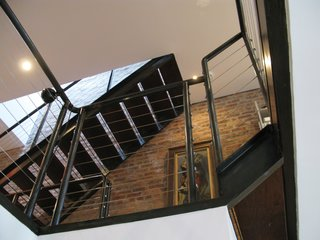 Parnass designed the home in layers rather than rooms, creating a fluid space filled with light from the large rear windows. Steel staircases and railings connect the spaces.