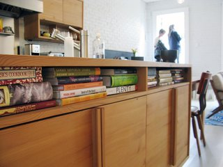 """Cubby holes under the kitchen counter house cookbooks. The cabinets are made from salvaged wood. """"The kitchen is where they like to be at home,"""" Bischoff says. """"That's why it's in the middle of the floor plan."""""""