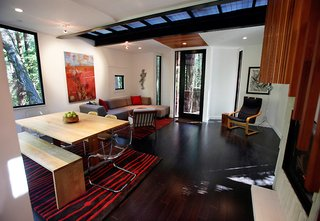"""The metal grating floor on the second story allows light to filter through to the first level (living room shown). """"You can sit or lay on the couch and see a 180-degree slice of the earth that you would just never see otherwise. It's a different perspective of the world,"""" says DeWitt."""
