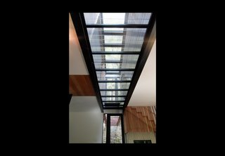 """A close-up shot of the glass """"spine."""" Fenster placed the units four feet apart from each other to allow light into the home. The grated bridge continues through the home to the outside path, integrating the structure with its landscape."""