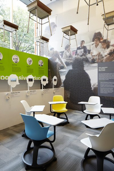 """In the Center for Architecture's double height gallery space, a grid of traditional school desks hang above a new, more flexible interpretation by Steelcase. There are also listening stations where visitors can hear the voices of 21st-century thinkers such as Katie Salen, James Paul Gee, and Howard Gardner, juxtaposed with key 20th century progressive educators whose contributions are listed behind.<br><br>Edgeless Schools takes into consideration how best to educate digital natives. """"All these kids are growing up knowing they can access at a very young age the information of the world on a hand held device,"""" Mellin says. """"What does that mean in terms of formal education? One thing that is agreed upon is that while no one knows how this will be played out, there is a great emphasis on flexibility, and being able to use spaces in a variety of ways."""" Photo courtesy the Center for Architecture."""