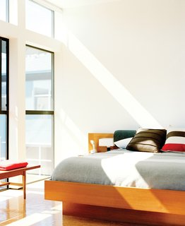 In the light-filled bedroom is a vintage teak coffee table and a Danish modern floating bed.