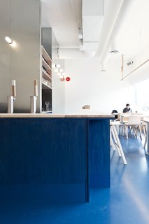 "Color is deployed to grand effect in the space. The achieve the cerulean hue, the architects specified commercial acrylic paint and developed a hand-rubbing technique to control the opacity. ""We're interested in common materials and creating space which is familiar and develops character and life with age,"" David says. ""We look forward to the blue wash and soaped surfaces wearing in and the painted floor being reapplied and thickened."""