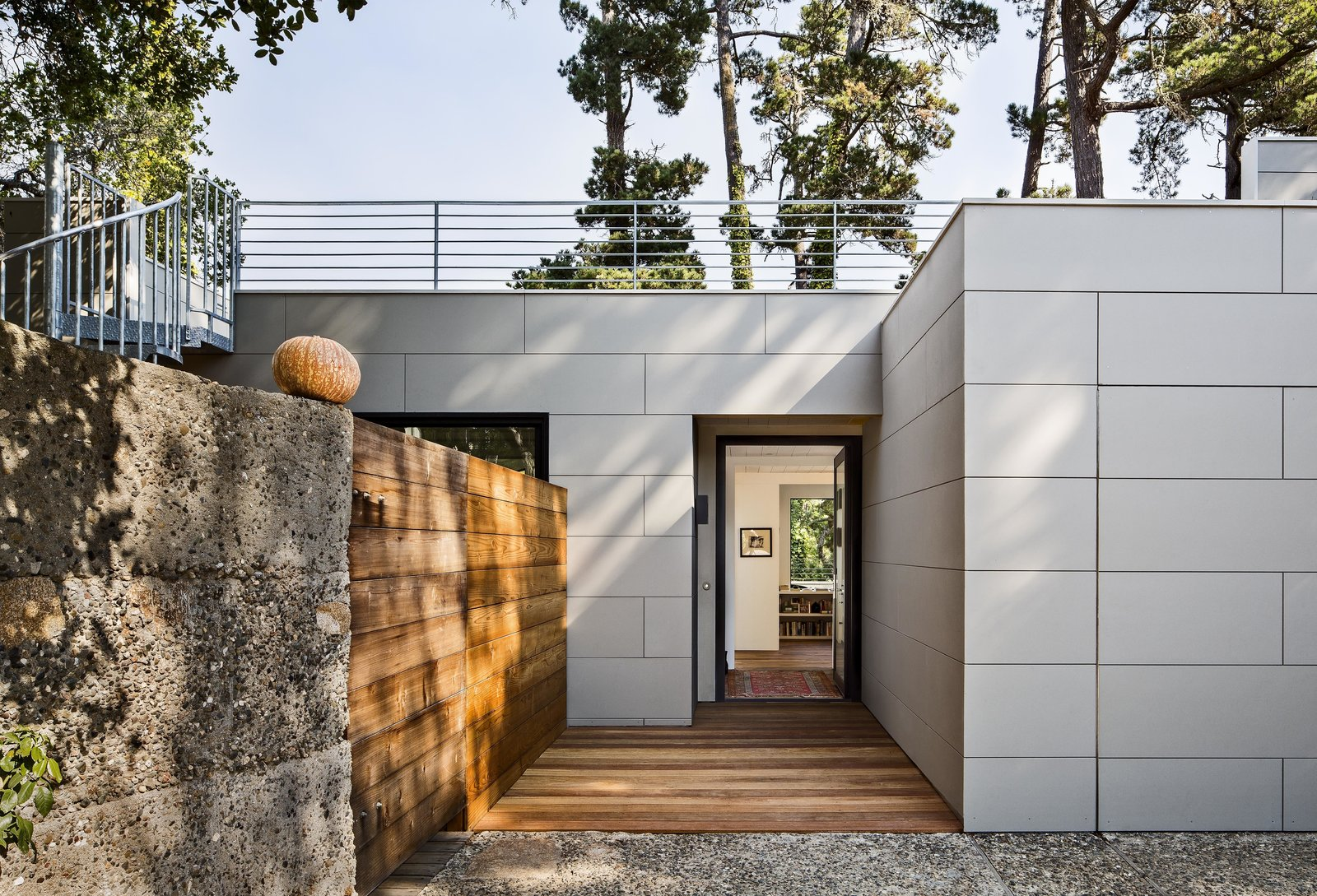"Architect Mary Ann Schicketanz transformed the old entryway into a private courtyard, replacing the door and window with a sleek glass slider. She removed the fiberglass panels and constructed a reclaimed wood barrier to separate the sitting area from the new front door on the opposite side. A high concrete wall also encloses it. ""I love that you can be right on the street without having any sense the street is there,"" Schicketanz says.  Photo 9 of 10 in Bright Renovation of a 1970s Big Sur Home from Smart Renovations That Use Reclaimed Materials"