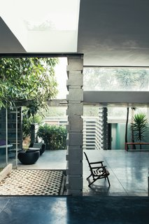Once past the main threshold, the house opens up to the outside, literally and figuratively. Three courtyards built around existing trees flow seamlessly into a series of rooms with glazed walls and sliding glass doors.