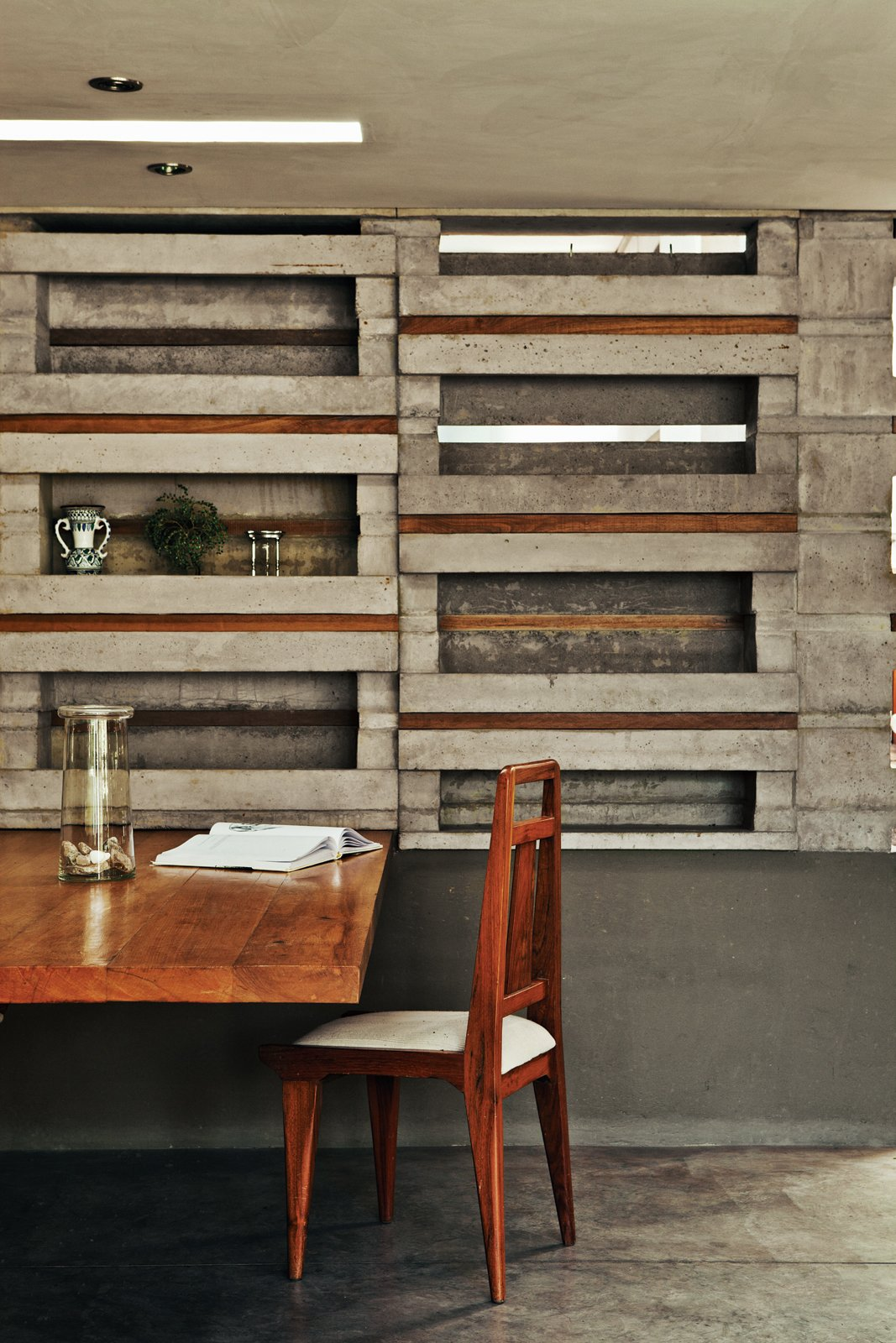 """""""With this flowerpot form we saw an opportunity to do everything using only a single piece of concrete,"""" says Sáez. """"It'sa simple, direct form of architecture.""""  A cantilevered slab of Colorado wood, secured in the gap beneath a concrete block, serves as a dining table. Pasternak paired this with a vintage chair made of rare Caoba wood. To fill other gaps between blocks, the architects alternated strips of wood with strips of Plexiglas that let in light from the adjacent kitchen.  Photo 3 of 10 in An Innovative Modular Building System in Ecuador"""