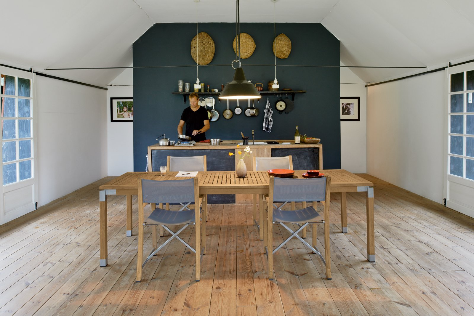 Kitchen, Wood Counter, Light Hardwood Floor, and Pendant Lighting In the kitchen area and throughout the home, Mads Odgård, shown here, and Mette Lyng Hansen mixed Odgård's pieces, such as the Odgård kettle for Raadvad and custom table, with Ikea basics  and the Workshop pendant lamp by Louis Poulsen.  Photo 4 of 12 in Modern Meets Traditional in a Swedish Summer House
