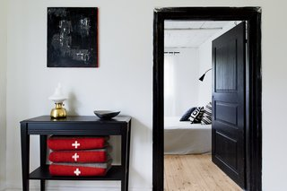 A black side table rests outside the bedroom hallway.