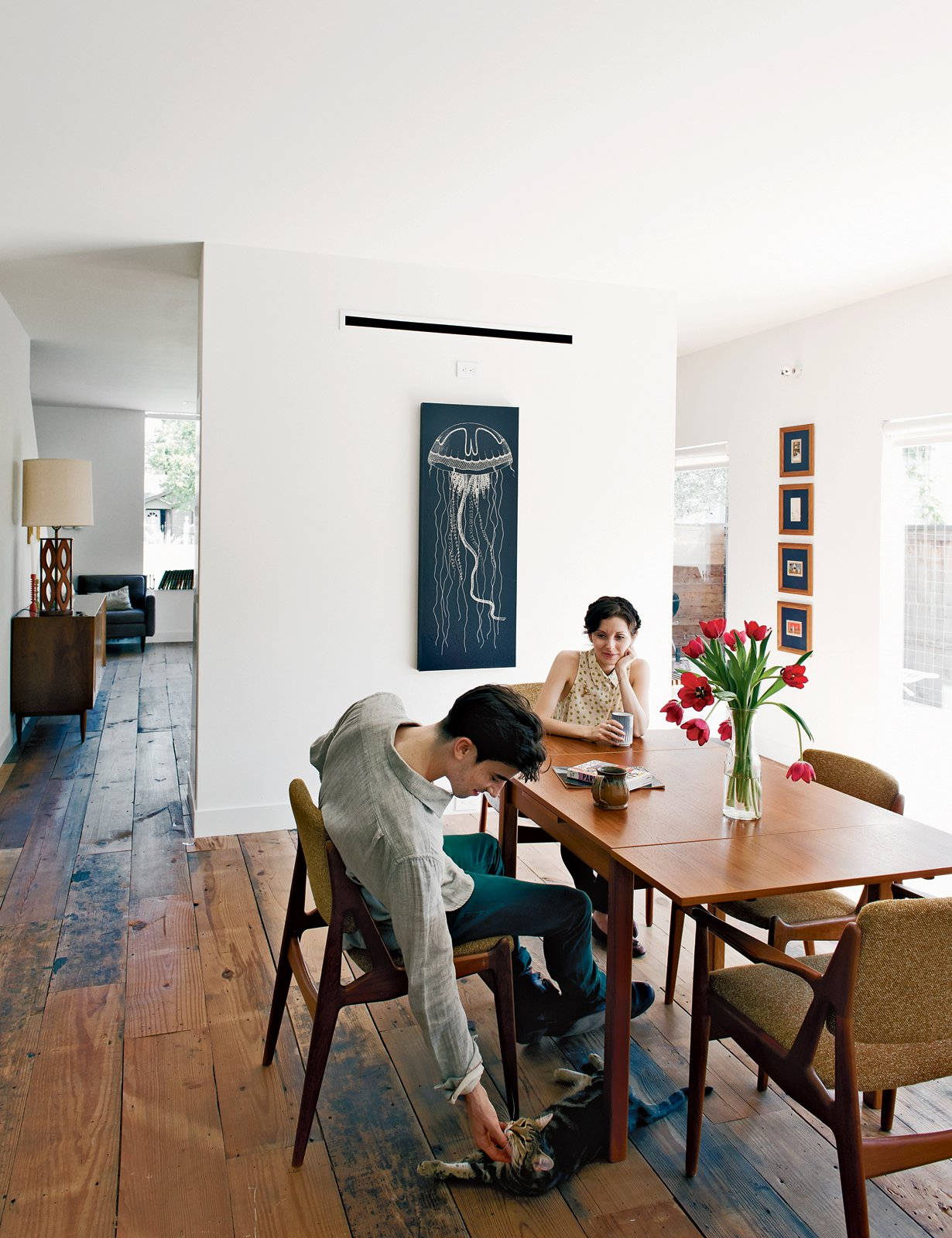 Dining Room, Table, Chair, and Medium Hardwood Floor Joseph Walsh and Lauren Strongin, seen here in their dining room, have also kitted out their unit with vintage furniture.  Photo 13 of 15 in Row on 25th: Affordable Housing Development in Houston