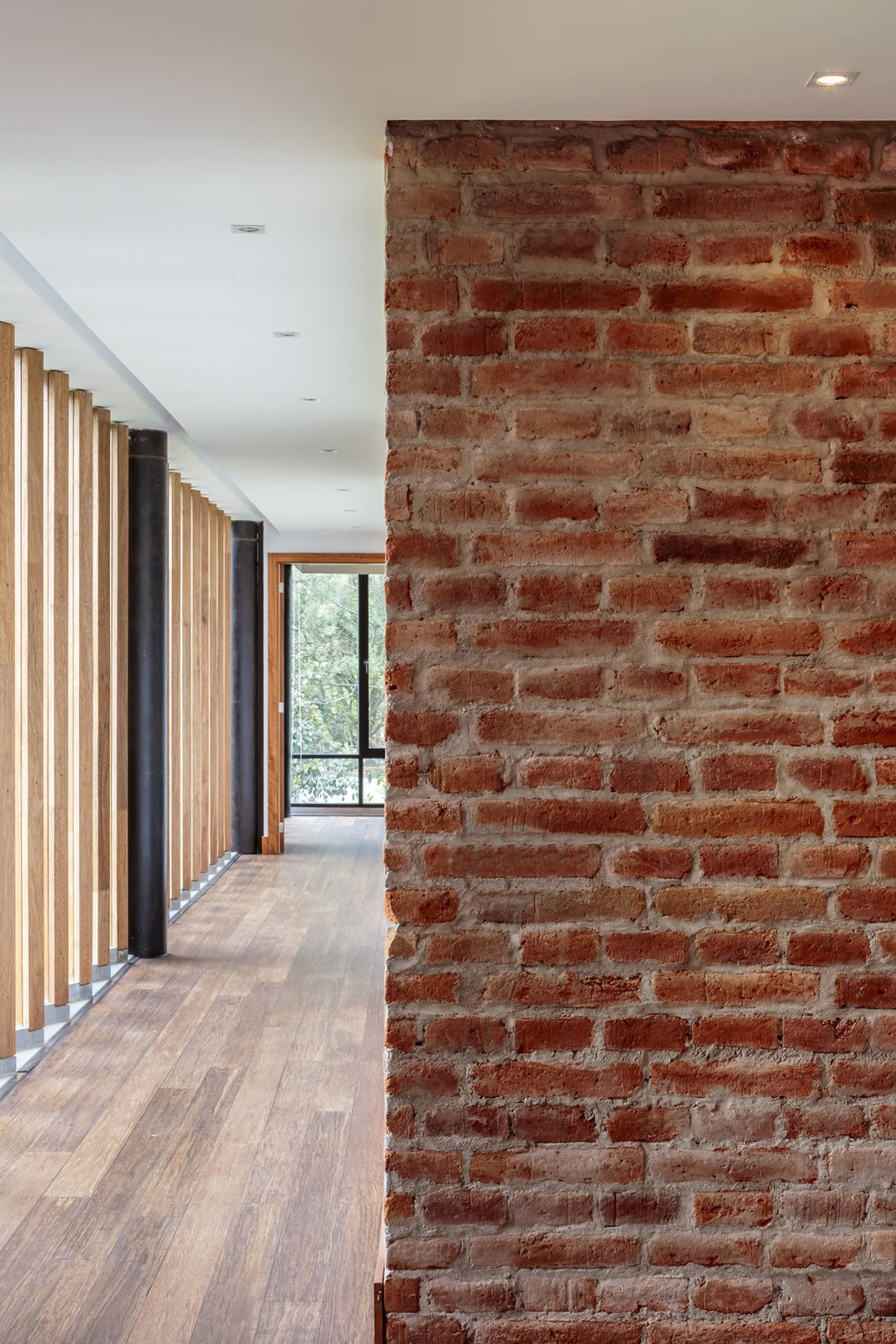 Hallway and Medium Hardwood Floor Burneo added exposed brick to his palette of interior materials.  Photo 6 of 10 in Revealing the Pros and Cons of Exposed Brick and How to Take Care of It from Uncle Knows Best