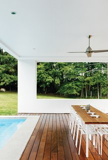 Cute Couple Alert: Modern Prefab Poolhouse Addition to a 1920s Sears Kit House - Photo 5 of 11 - The residents scored the Saarinen-style table at Brimfield Antique Show for only $200. A Java ceiling fan by Minka-Aire helps circulate the breeze on the pool patio. The decking is made of six-inch-wide Garapa with hidden fastening clips. The dining chairs are from Ikea.