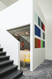 An installation by Willem Cole hangs in the gallery, which leads to an open stairway to the office and private bedrooms upstairs.