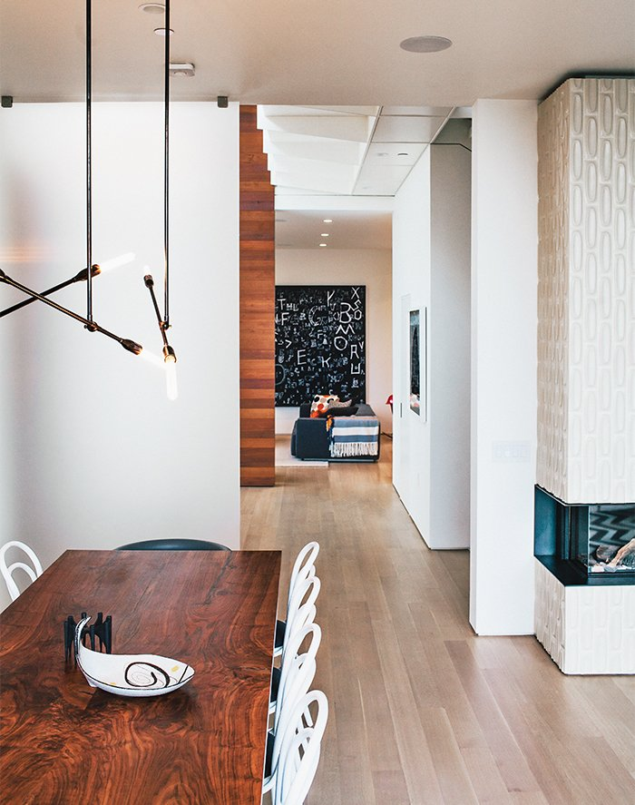 The catwalk above leads to the master bedroom. The living-dining room's Stix chandelier is from Nido Living. Tagged: Dining Room, Table, Chair, Pendant Lighting, and Corner Fireplace.  Photo 6 of 19 in A Home with Eclectic Style Looks Just Right