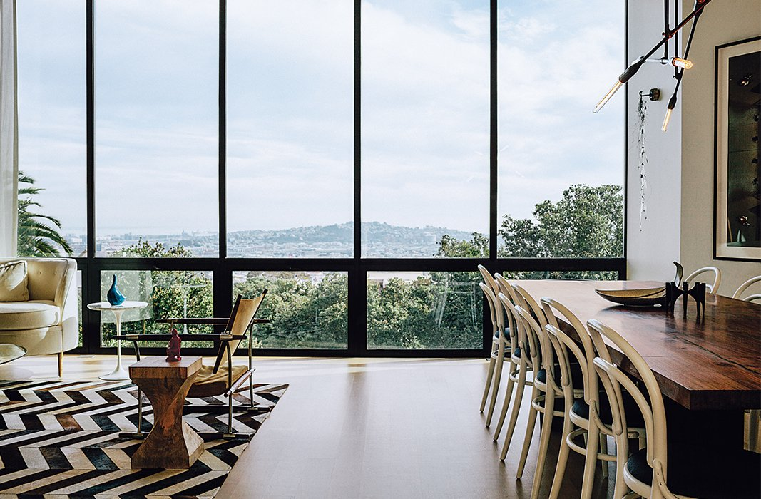 Dining Room, Table, Chair, Pendant Lighting, Light Hardwood Floor, and Rug Floor The living-dining room overlooks the neighborhood and the Bay beyond. The Safari chair was designed by Jens Quistgaard. Michael Thonet chairs are paired with a walnut table by Anthony Marschak for Original Timber Co.  Photo 7 of 19 in A Home with Eclectic Style Looks Just Right