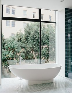 The bathroom features a tub by Benedini Associati for Agape, Dornbracht tub filler, and retractable shades.