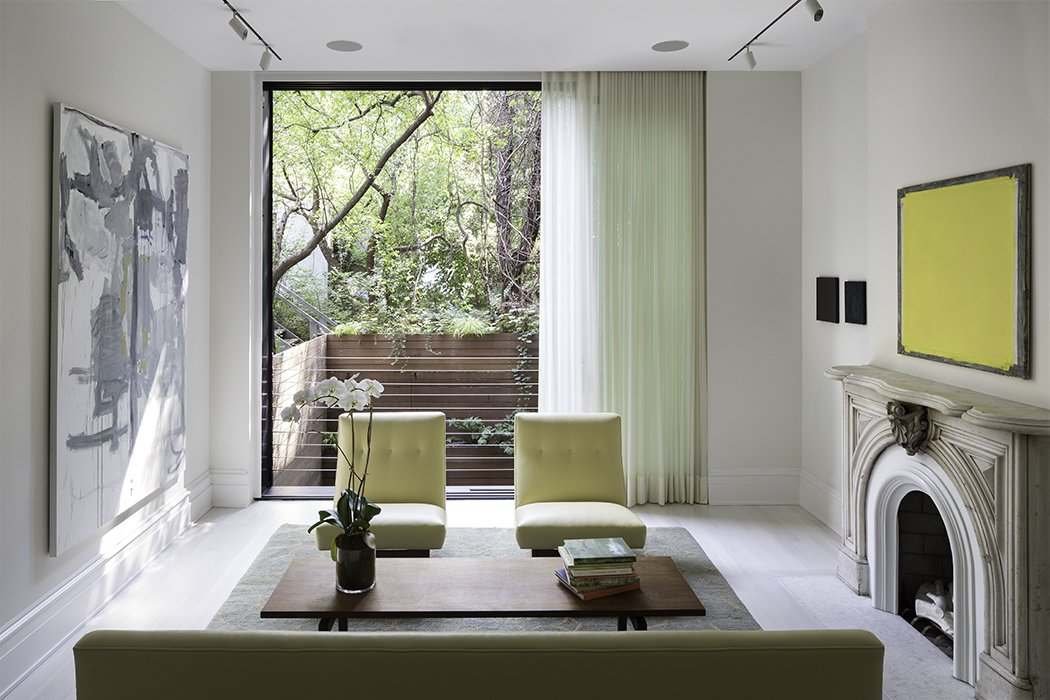 "The West Village renovation was the second project Lubrano completed for her client. ""She is a collector of contemporary art and has minimalist design sensibilities, so she was not necessarily interested in reiterating typical attitudes of how a historic townhouse should present itself,"" Lubrano says. ""This residence creates a mood that is queued not through a rote familiarity, but through a pleasure in precision and a confidence in form making.""  One of the main challenges was integrating the interiors with the outdoor areas—a luxury in dense Manhattan. On the parlor floor, a floor-to-ceiling window overlooks the patio. Tagged: Living Room, Chair, Coffee Tables, Ceramic Tile Floor, Track Lighting, Sofa, Standard Layout Fireplace, and Wood Burning Fireplace.  Photo 4 of 7 in A Sophisticated Renovation of a 19th Century Manhattan Town House"