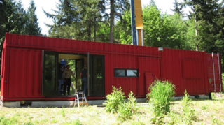 8 Companies That Are Revolutionizing Kit Homes - Photo 9 of 9 - Repurposed shipping containers serve as the primary materials for the houses and working spaces designed by ShelterKraft. The company's designs focus primarily on disaster relief projects, drawing from existing steel frames and skins in order to reduce the use of new materials. Their buildings range from small cargo cottages of 160-square-feet to 700-square-foot warehouses for industrial facilities. Alhough they come with electric power, heat and plumbing, they generally require a pre-existing concrete foundation and a local contractor to ensure a smooth, safe installation.