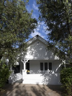 "The façade of the interwar dwelling was painted bright white and left largely unchanged, with a sole burst of color coming from a yellow DesignByThem ""tomtom"" letterbox. Though the extension is invisible from the street, architect Christopher Polly says it provides ""significant additional freedom for the owners and their three young children to grow into."""