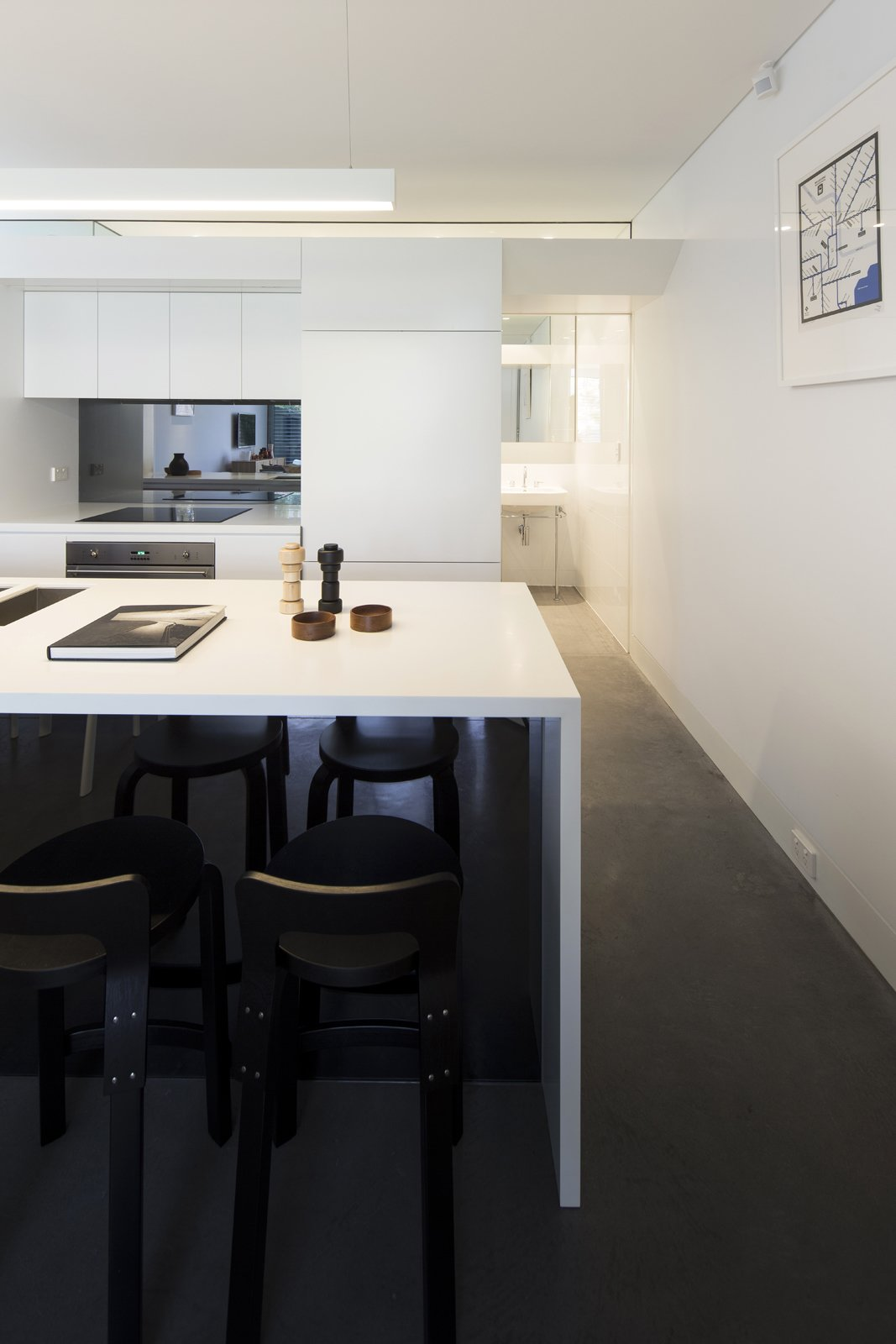 Casual meals are eaten at the kitchen's glacier white Corian countertop, which features Aalto K65 stools. The island's Blanco sinks offer a direct, uninterrupted sightline to the garden.  Photo 5 of 9 in Renovation Near Sydney Opens Home Onto a Lush Garden