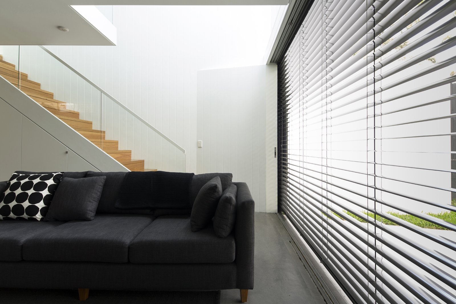 When the sun is at its brightest, the east-facing glass wall is shielded by retractable Horiso venetian blinds that have been powdercoated to match the extension's charcoal cladding.  Photo 7 of 9 in Renovation Near Sydney Opens Home Onto a Lush Garden