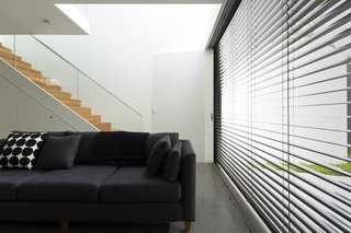 When the sun is at its brightest, the east-facing glass wall is shielded by retractable Horiso venetian blinds that have been powdercoated to match the extension's charcoal cladding.