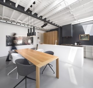 The kitchen area was built around the concept of different surfaces working together: stainless steel countertops for work, white Corian for preparation, and solid white oak for storage. A landscape painting by Chabauty's grandfather hangs above the sink, adding a note of serenity to the room. The kitchen contains a Viking range and oven, a Bosch 800 Plus Series dishwasher, a KWC Eve faucet, a Liebherr HRB 1100 refrigerator. Artek A110 Pendants hang above the dining table, a custom oak piece surrounded by chairs from HAY.