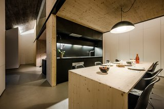 The kitchen uses laminated chipboard for the countertop and cabinets, and the same plywood used throughout the house for the table. The lamp is IKEA.