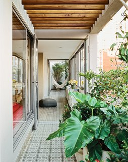 Amazing Garden Oasis in São Paulo Born from a Five-Year Search and Renovation - Photo 13 of 15 - A cement-tile floor carves a path through the dining room as it runs the length of the apartment, blurring the boundary between inside and out.