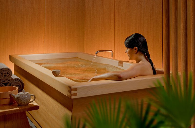 Zen BathWorks strengthened this large tub with an apron that doubles as a cup rest. The room's walls are wood-clad to reduce visual clutter and the tub rim is indented to direct water towards a floor drain shared by a shower. Soaking tubs are often smaller than conventional tubs as the bather sits with knees to chest-great if you have a small bathroom but want a tub. Sides can be sloped or straight and wood with knots generally costs less than straight-grained planks.  If you're curious about cedar's scent, the bars sold in hardware stores for use as a moth-repellent give a general idea. Photo courtesy of: Zen BathWorks  Photo 10 of 13 in Japanese Soaking Tubs