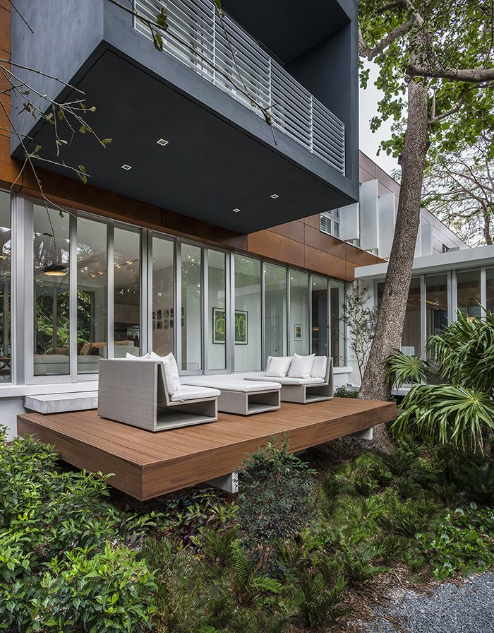The cantilevered upper volume shades a deck on the ground floor. Tagged: Outdoor, Small Patio, Porch, Deck, Wood Patio, Porch, Deck, and Back Yard.  Photo 3 of 12 in This Modern Miami House Feels Like It's in the Middle of the Jungle