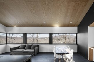 """The horizontal strip window in the combined living and dining room frames the wooded mountain range and valley, transforming the home's interior with the changing seasons. It also saved money during the construction process, as the minimal glazing cost a lot less than floor-to-ceiling windows. """"It lets you enjoy the spectacular views without breaking the bank,"""" Dworkind says."""