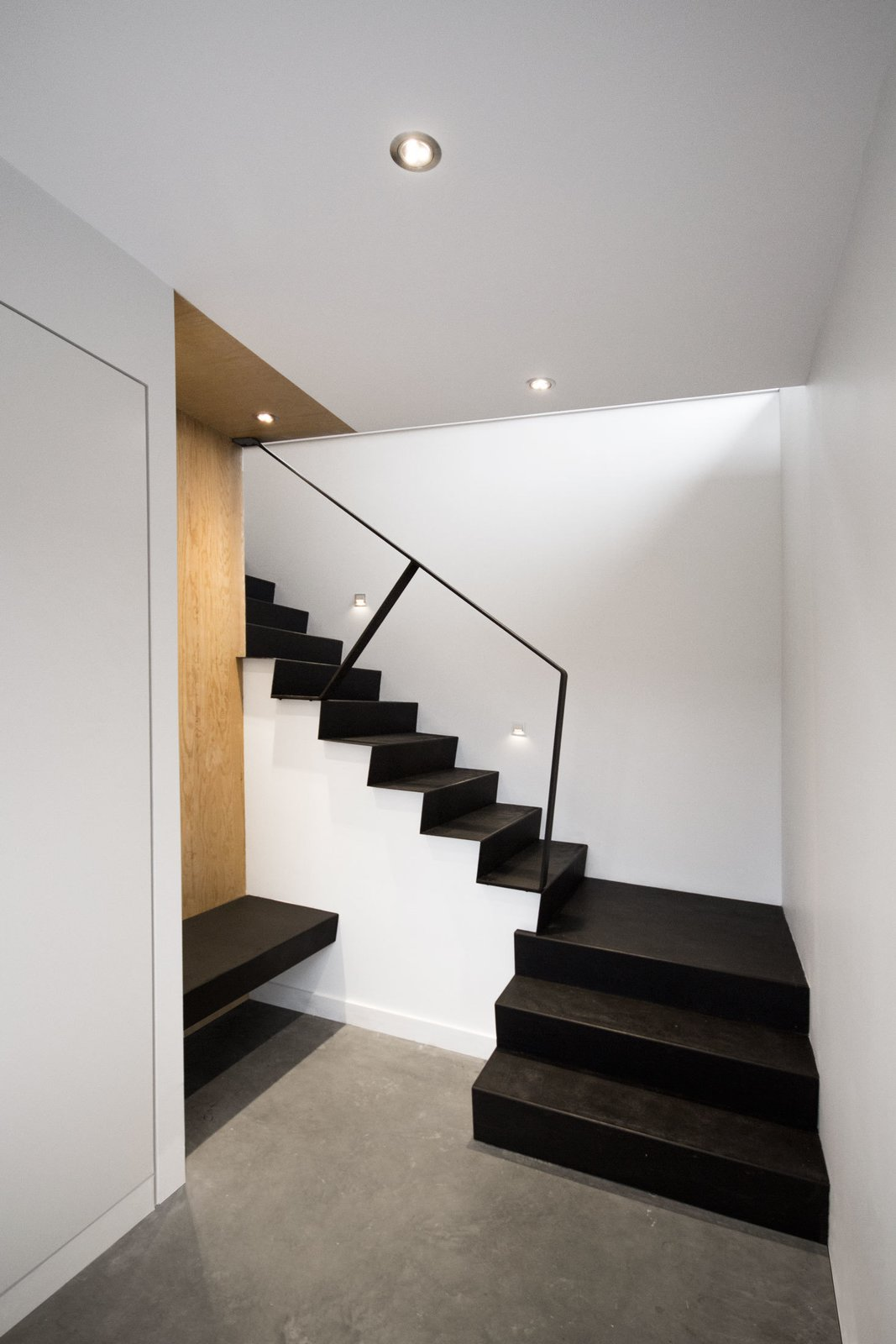 Staircase and Metal Railing The staircase was built using standard wood frame construction with plywood treads. Each step was then covered with a thin sheet of folded steel that outlines its angled profile.  Photo 7 of 11 in Amazing Cantilevered Home in the Mountains