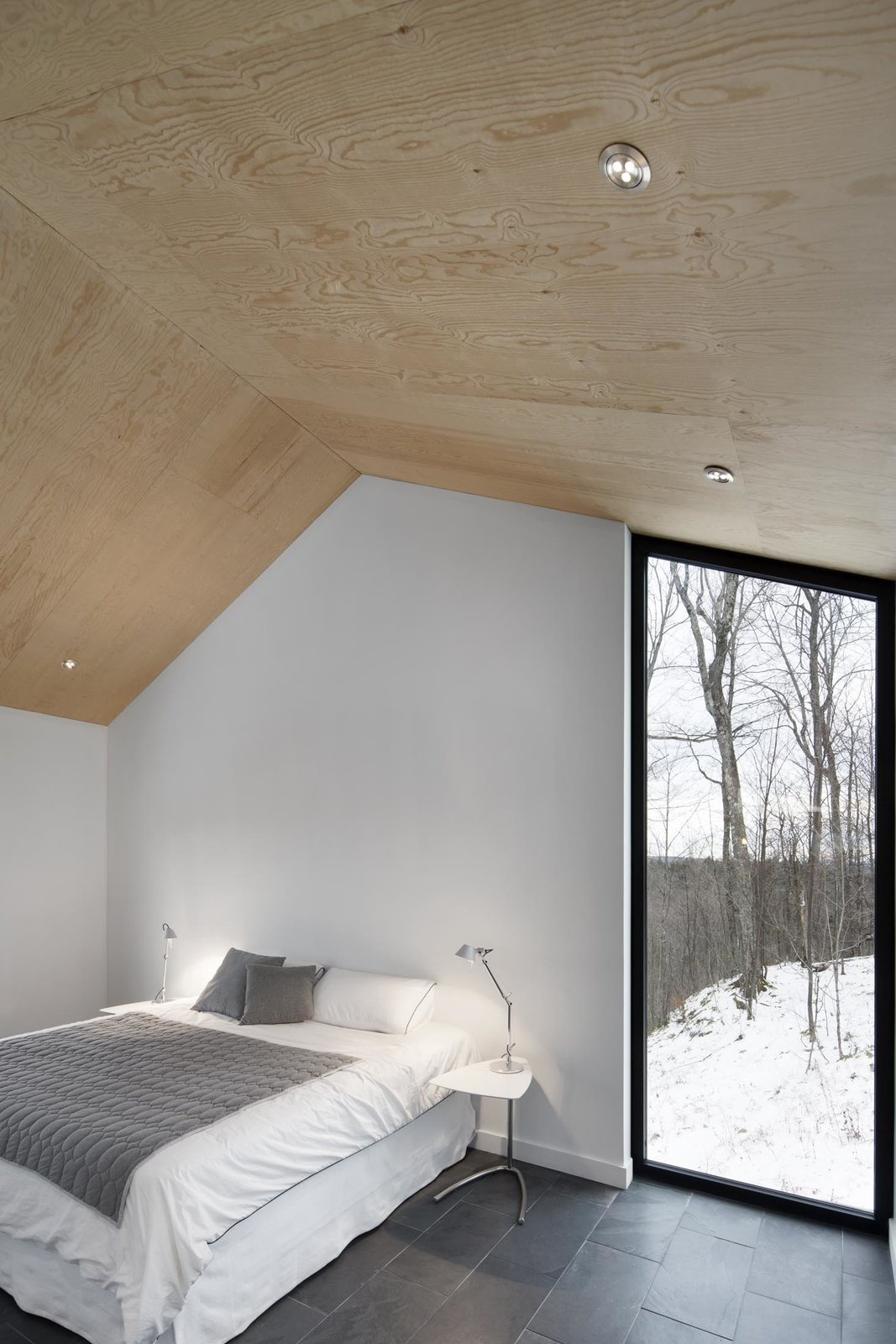 Bedroom, Table Lighting, Bed, and Slate Floor The bedroom's vertical, floor-to-ceiling window lets occupants admire the graceful trees outside. A Mini Tolomeo lamp by Artemide sits on the bedside table.  Photo 9 of 11 in Amazing Cantilevered Home in the Mountains