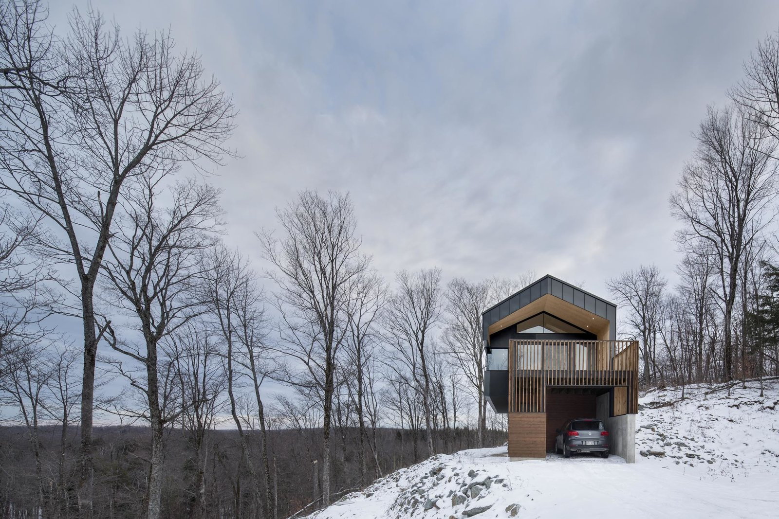 The home's lower level serves as a garage, allowing direct access to the house. Tagged: Attached Garage, Exterior, House, and Metal Siding Material.  Photo 10 of 11 in Amazing Cantilevered Home in the Mountains