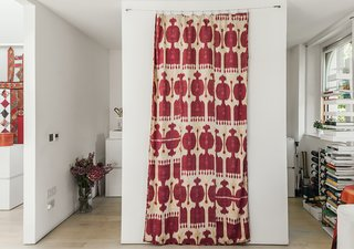An American Ex-Pat Renovates a Tiny London Apartment on Her Own Terms - Photo 6 of 14 - A handwoven silk ikat print, which Molineus acquired in Uzbekistan, is draped between the kitchen entrances. A Sapiens bookshelf by Bruno Rainaldi stands at far right.