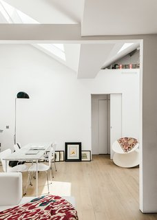 An American Ex-Pat Renovates a Tiny London Apartment on Her Own Terms - Photo 8 of 14 - The living area is furnished with a marble table that Molineus designed, ringed with Series 7 chairs by Arne Jacobsen for Fritz Hansen and bookended by a Mezzaluna Terra floor lamp by Bruno Gecchelin and a Spun chair by Thomas Heatherwick for Magis.