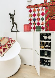 The custom shoe cabinets at the top of the stairs double as a balustrade.