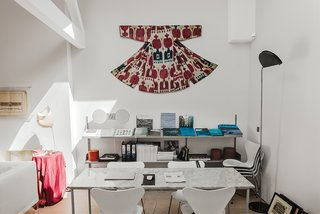 An American Ex-Pat Renovates a Tiny London Apartment on Her Own Terms - Photo 11 of 14 - Above the 606 Universal shelving by Dieter Rams for Vitsœ, Molineus displays a Central Asian ikat wedding garment that dates to around 1900. The Gaku floor lamp at left is by Dagmar Mombach and Ingo Maurer.
