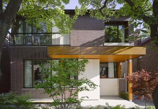 Smart Tech Makes this Modern Home Ultra Energy Efficient - Photo 1 of 11 - Located in Toronto, the Bedford Park House embodies an architectual hat trick: it's smart from a technological standpoint, it's energy efficient, and it's designed so the residents, a doctor and his wife, can age in place. Architect Alex Tedesco, a senior partner at LGA Architectural Partners, created a thoughtful design grounded in the advanced building science and that embodies the principles of modernism. The facade is clad in Rum Raison Velour brick by Belden with Douglas fir accents.