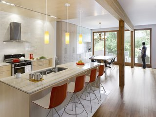 """The kitchen is outfitted with a duel-fuel range by Bosch, a Diamonte Canopy hood by Faber, a LaPerla dishwasher by Miele, French-door refrigerator by LG, Blanco sink, and Compact Smart overn by Breville. Catifa 46 stools by Arper are stationed at the bar. The counters are quartz and the cabinets are solid maple. """"Given that the owners' intention was to stay and age in the house, we decided that the materials needed to be elegant and timeless and, in essence, could also age well in place,"""" Tedesco says. """"This led to devising a refined and warm palette of natural finishes. White carrara marble, oiled clear Douglas fir, and maple floors and millwork create a light, warm interior with a reddish hue that emanates when the sunlight washes the woods. The selection process included R-and-D on the materials to assess their ability to be both robust enough to handle every day wear and tear in the short term and acquire a beautiful patina long term. We also researched MSDS charts to ensure they were safe, non-toxic, and would not off-gas."""""""