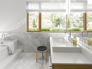 Carrara marble clads the spacious bathroom.