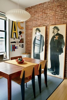 "The Vladimir Lenin prints were a gift from Drew's father, also a graphic designer, and reflect their shared love of ""graphically powerful types of printed ephemera,"" Drew says. Standard chairs by Jean Prouvé for Vitra are tucked under the dining table."